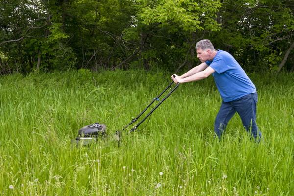 Man Cutting Tall Grass